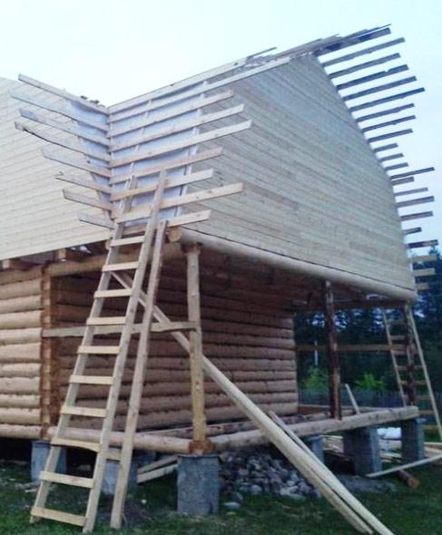 Дом из бревна ручной рубки с большой мансардной крышей
